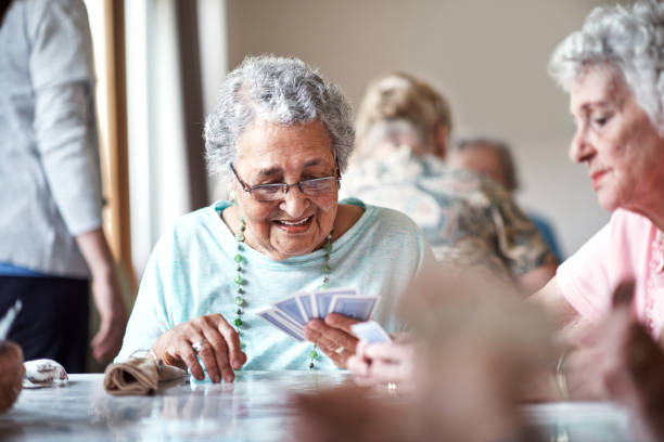 I can't lose with this hand Shot of a group of seniors playing a board game in their retirement home recreational pursuit stock pictures, royalty-free photos & images