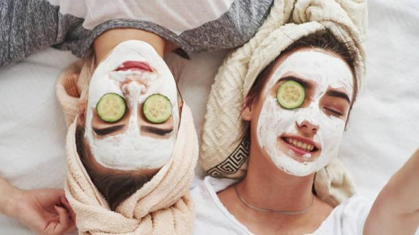 Kann mein Auge nicht öffnen. Konzeption der Hautpflege mit frischen Gurkenringen und weißer Maske im Gesicht. Zwei Schwestern haben Wochenende im Schlafzimmer – Foto