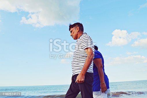 An elderly couple taking a walk by the sea on a beach. The couple is in their sixties. Stand in close proximity to each other. The lady is in blue top and white trousers and the man is in striped white polo neck t- shirt . A wave splashes at the shore. The lady is hidden behind the man