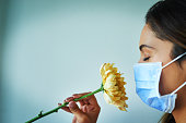 Shot of a young woman smelling a flower while wearing a surgical mask