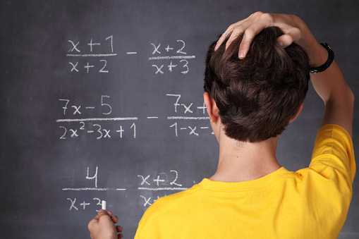 Young student scratching his head in front of blackboard