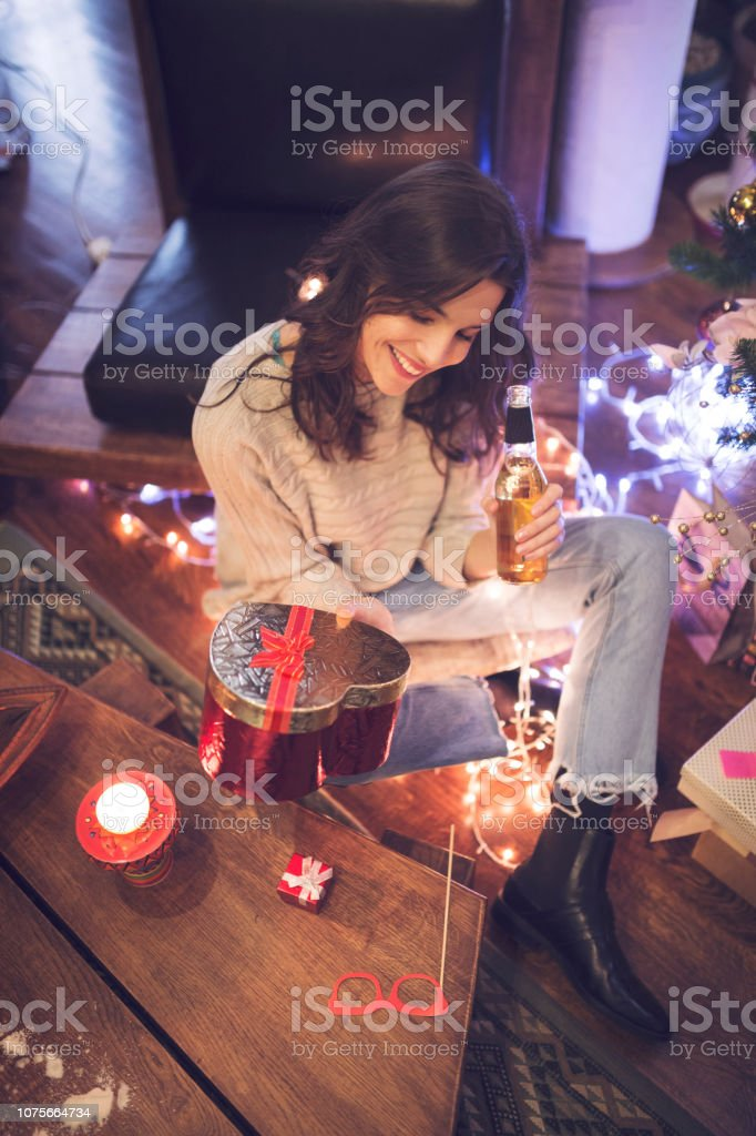 Smiling women enjoying a beer and holding a gift box.