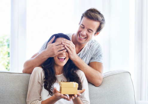 A young boyfriend covering his girlfriend's eyes as he gives her a present