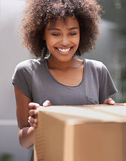 I can't wait to see what it is Shot of a young woman receiving a package clothes in box stock pictures, royalty-free photos & images
