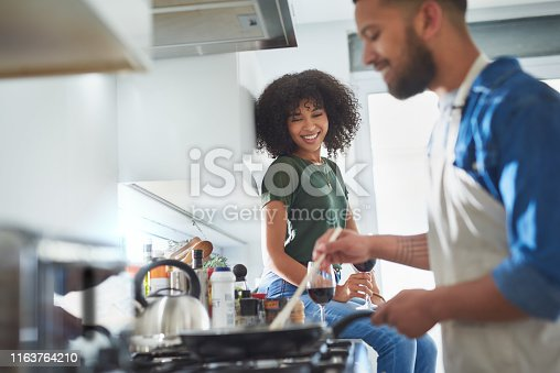 Shot of a happy young woman watching her husband prepare a meal at home