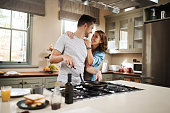 Shot of a young woman embracing her partner while he cooks breakfast