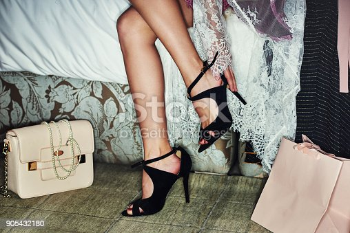 Shot of a young unrecognizable woman putting on high heel shoes that she bought while being seated on a bed
