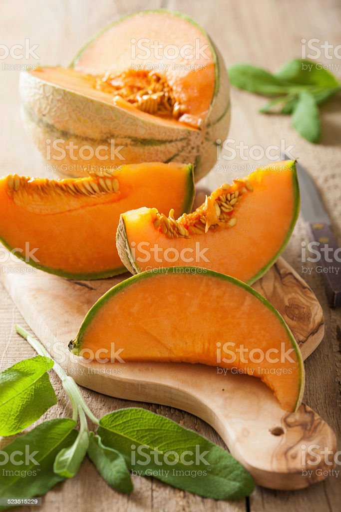 cantaloupe melon sliced on wooden background stock photo