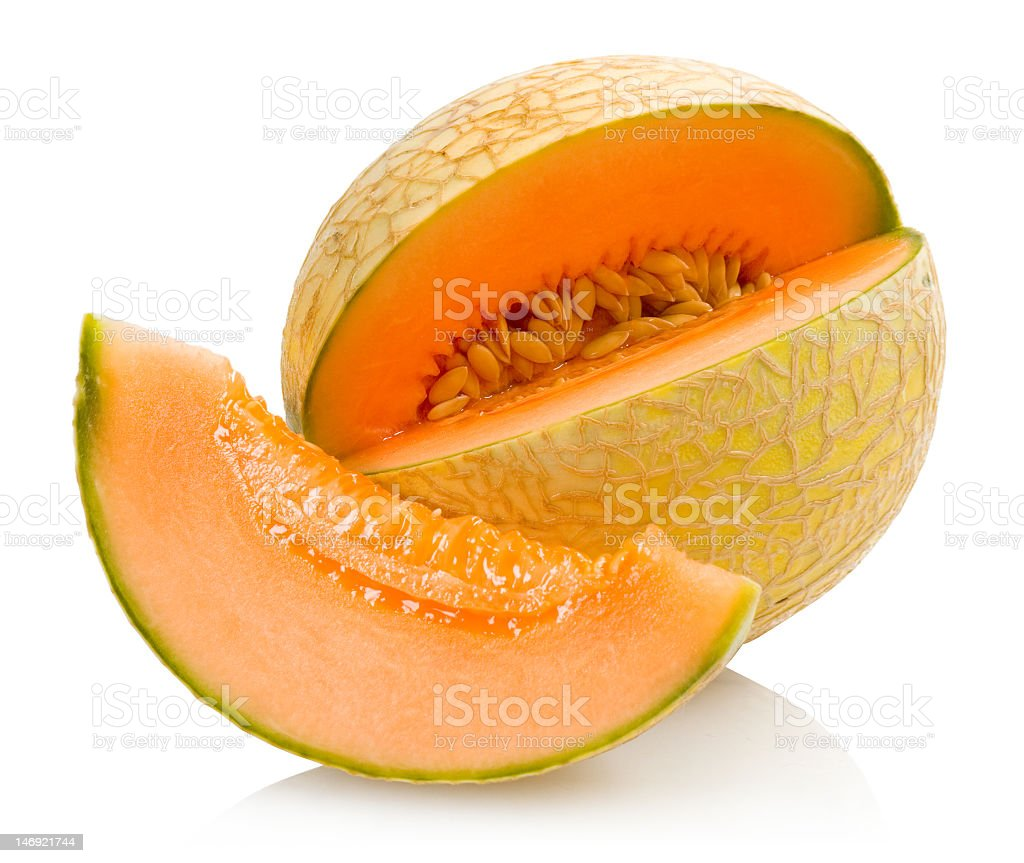 Cantaloupe with a slice cut out of it on a white background stock photo