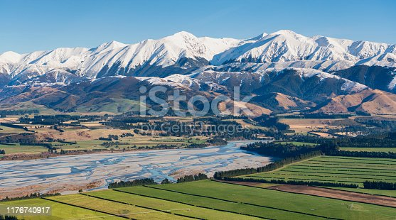 An elevated view of the Waimakariri River and the farmlands of the Canterbury Plain, on New Zealand's South Island. In the background we see the mighty Southern Alps.