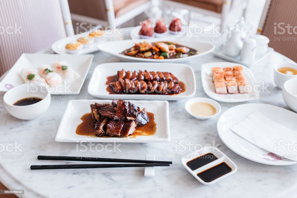 Cantonese meal including BBQ Pork, Roasted Duck, Fresh Shrimp Spring Rolls, Deep fried snapper fillets with XO Sauce and sweets on marble top round table. stock photo