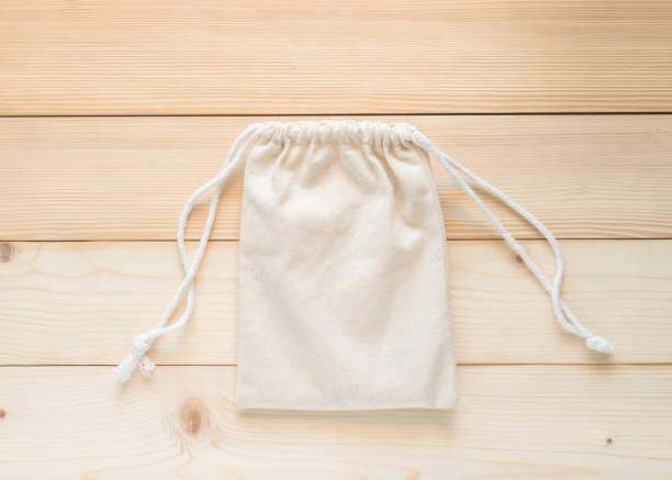 canvas tas met koord, mockup voor kleine eco zak gemaakt uit natuurlijke katoenen stof doek plat lag op witte houten achtergrond van bovenaanzicht - zak tas stockfoto's en -beelden