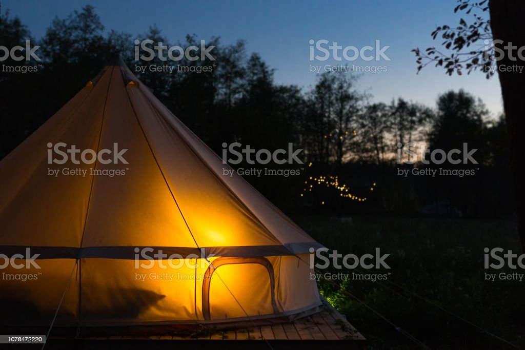 Canvas glamping tent glows at night stock photo