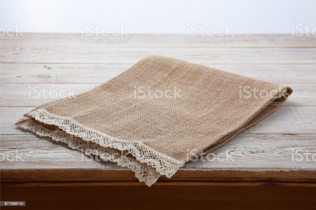 Canvas napkin with lace. Burlap hessian sacking on white wooden table background top view stock photo