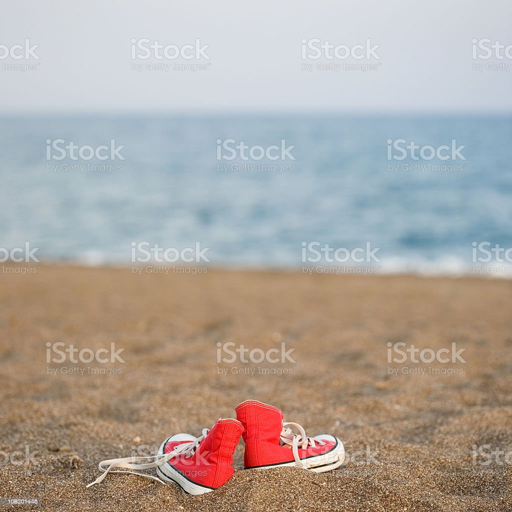 Canvas shoes on the beach stock photo