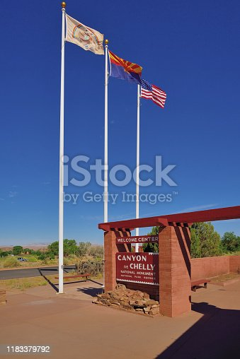 Just the Canyon de Chelly welcome center with the flags of the US, Arizona and the Navajo Nation against the brilliant sky and colors in the great american deserts of the southwest, The leftmost flag is that of the Navajo Nation which co-owns Canyon de Chelly National Monument