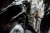 istock A canyoneering male making an abseil down the static rope into a dark stone cave 1190355752