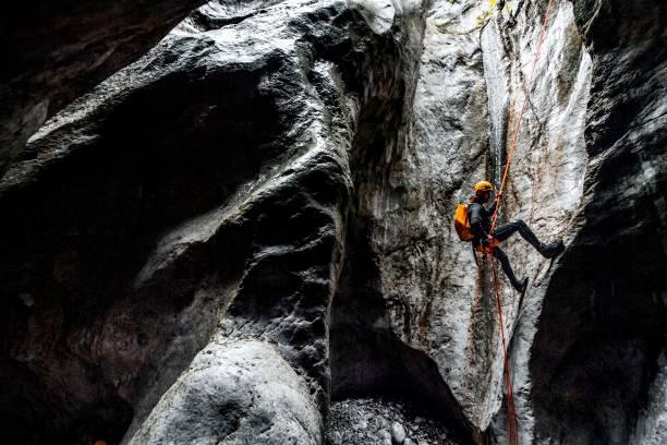 Ein Canyoneering-Männchen, das das statische Seil hinunter in eine dunkle Steinhöhle abseilen lässt – Foto