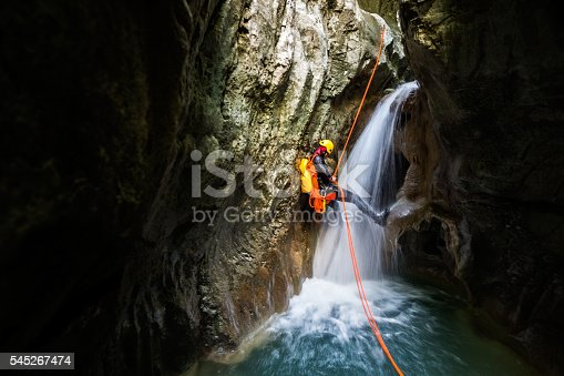 Canyoneering member with backpack rappeling down the small waterfall in the canyon.