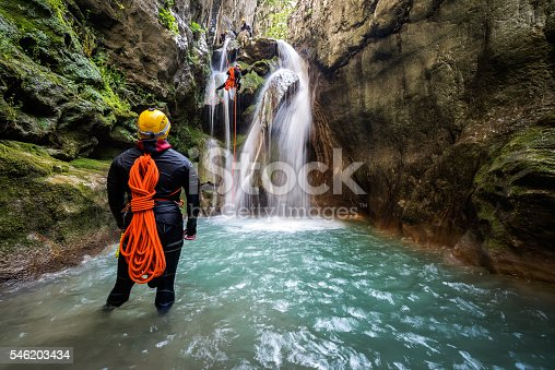 Canyoneering team member with backpack rappeling down the waterfall in the canyon while man in front view and others on top of the waterfall are on stand by.