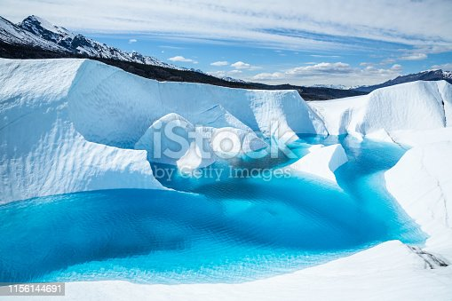 Crystal blue waters of a supraglacial lake on the Matanuska Glacier fills in narrow canyons and fins of ice, or seracs, jut out from the deep blue waters.