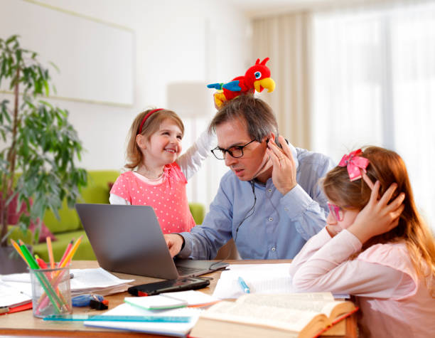 Caos - Father And Schoolgirl Working At Home - Telework And E-Learning stock photo