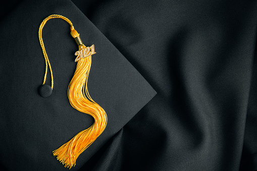 A class of 2021 tassel on a black cap and gown.