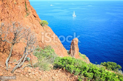 Sailboat in the Mediterrean at the peninsula Cap du Dramont near Frejus. The Cap du Dramont lies at the scenic coast road Corniche d'Or between Cannes and Frejus at the French Riviera below the Massif d'Esterel. It has the same red porphyry stones as the Massif d'Esterel.
