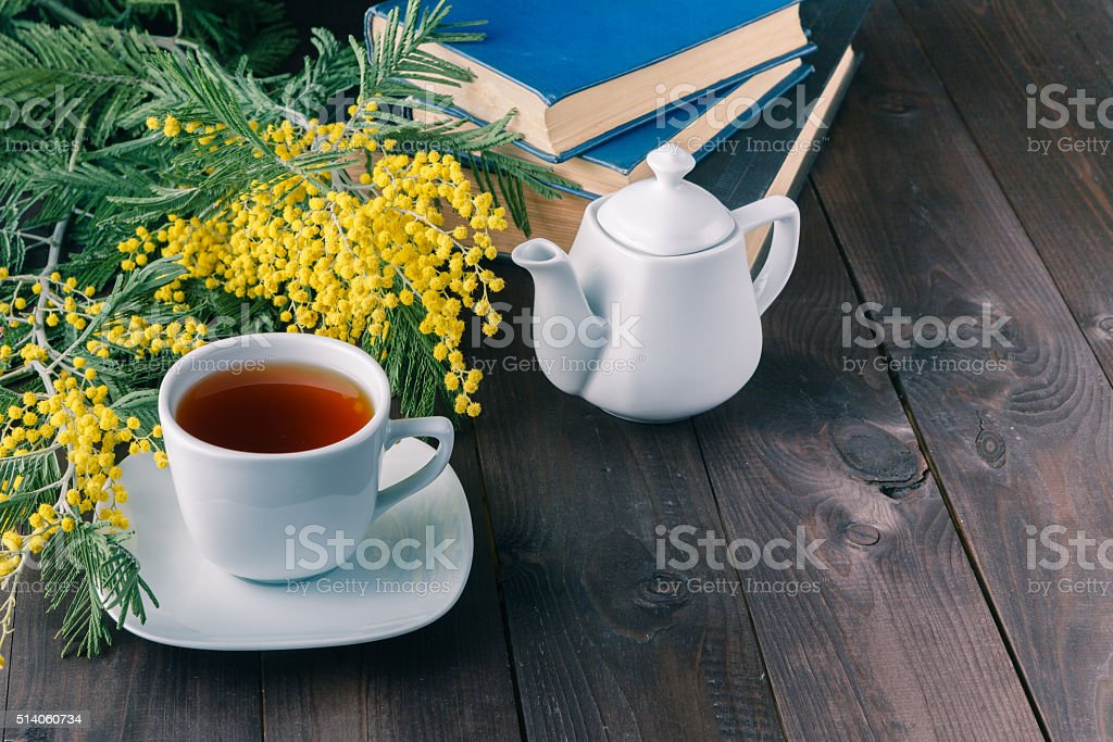Cap of tea and book on the table top stock photo