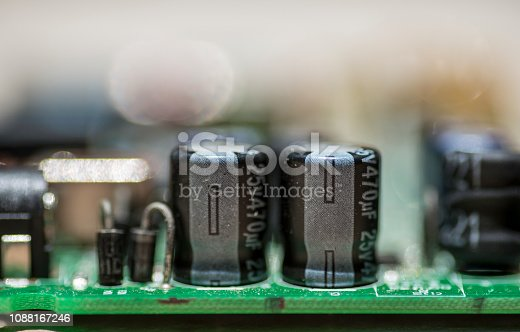Macrophotography of printed circuit with capacitors and connectors on green board.