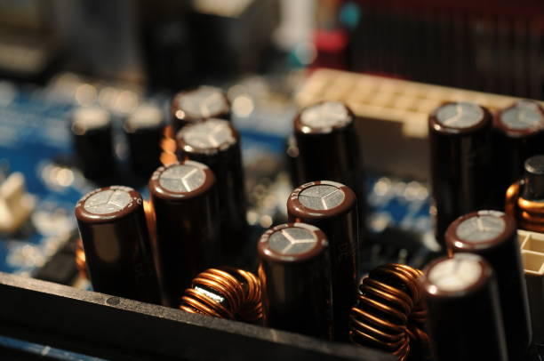 capacitors components closeup on a computer motherboard - capacitor stock photos and pictures