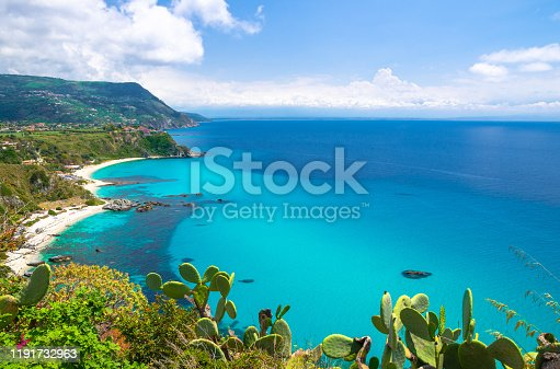 Cape Capo Vaticano Ricadi aerial view from cliffs platform, sandy beach, green mountains, Sicilia island, blue sky white clouds background and cactus plants foreground, Calabria, Southern Italy
