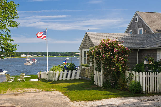 Cape Cod Summer Day A seaside cottage on a quiet cove on Cape Cod features a, arbored gate covered with pink roses. cape cod stock pictures, royalty-free photos & images