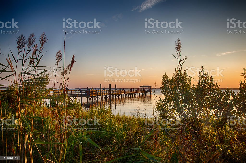 Cape Fear River The pier on the Fort Fisher Recreation Area near Kure Beach, North Carolina with the sunsetting in the distance. Beach Stock Photo