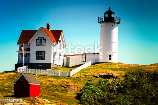 Cape Neddick (Nubble) Lighthouse York, Maine,USA. Red-roofed white buildings, blue sky with white clouds. Gentle rolling landscape with rocky terrain.