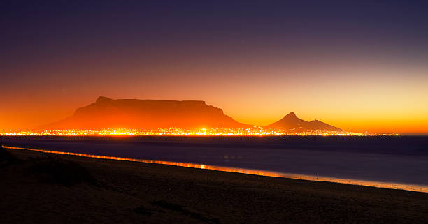Cape Town and Table Mountain by night, ablaze with light Shot with long exposure, one hour after sunset, the city lights of Cape Town shimmer in front of the iconic Table Mountain and are reflected in Table Bay. Shot with Canon EOS 1Ds Mark III.  ablaze stock pictures, royalty-free photos & images
