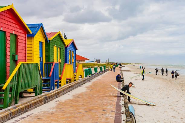 cape town, south africa, 28. september 2013, bunten strandhäuschen und surfer - küstenfamilienzimmer stock-fotos und bilder