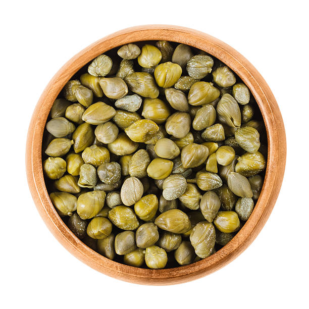 Capers in wooden bowl on white background stock photo