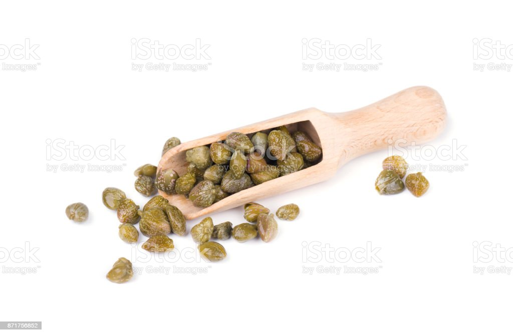 Capers in wooden spoon isolated on white background. Pickled capers. Canned capers stock photo