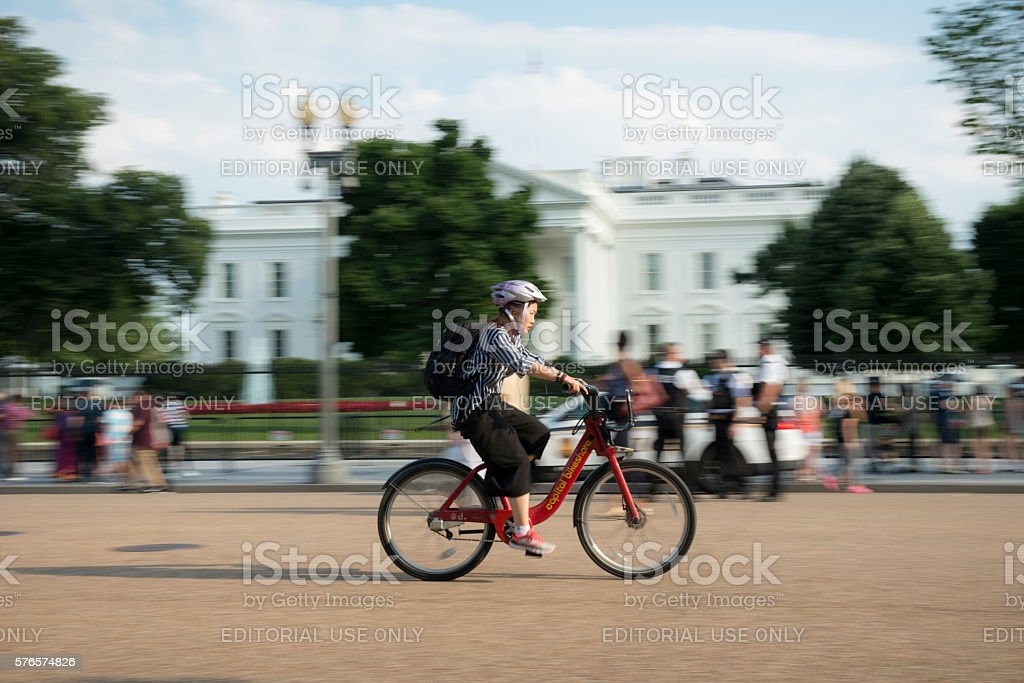 Capital bikeshare bicycle riding past White House stock photo