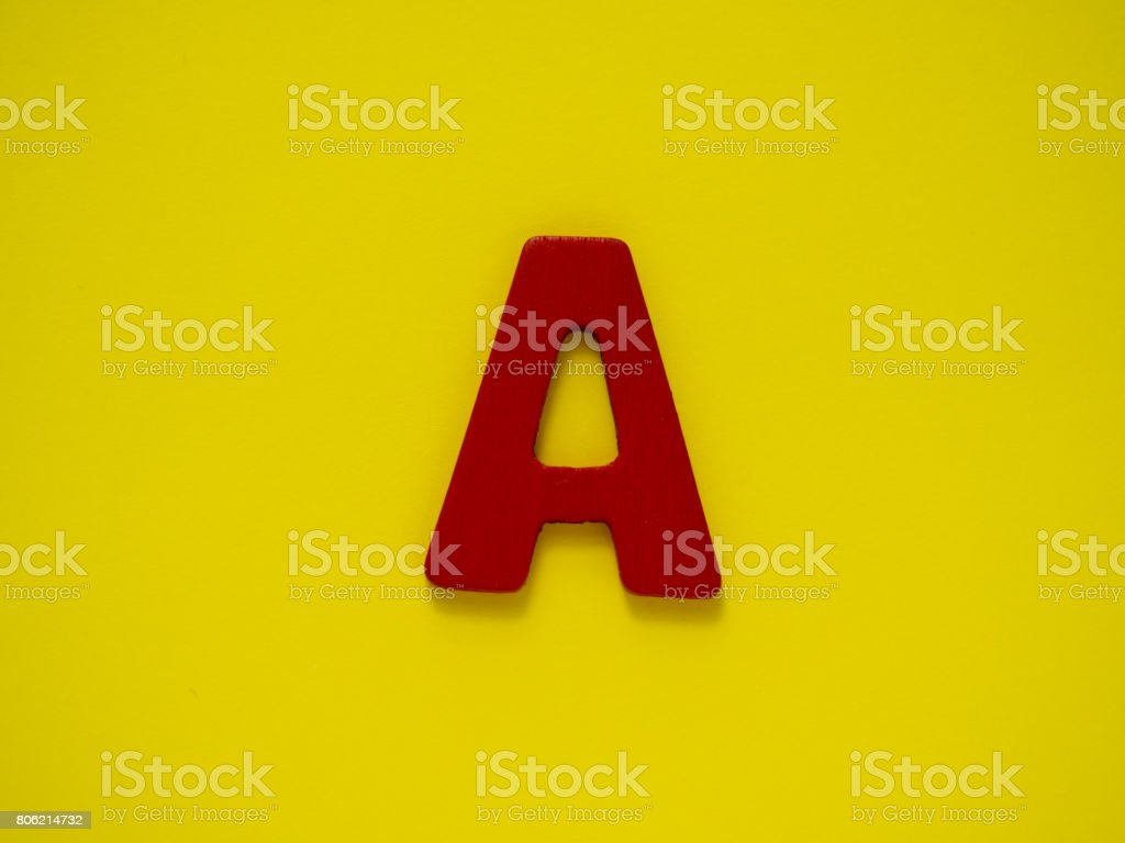 Capital letter A. Red letter A from wood on yellow background. Alphabet vowel. stock photo