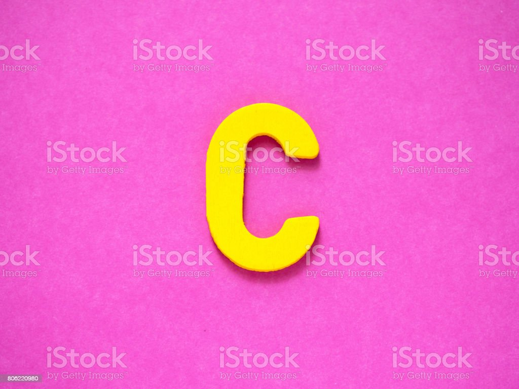 Capital letter C. Yellow letter C from wood on purple background. stock photo