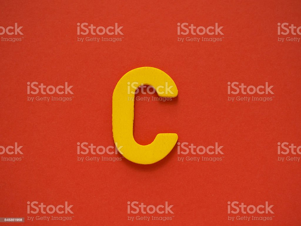 Capital letter C. Yellow letter C wood on red background. stock photo