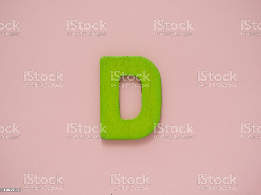 Capital letter D. Green letter D from wood on pink background. stock photo
