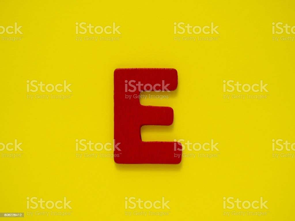 Capital letter E. Red letter E from wood on yellow background. Alphabet vowel. stock photo