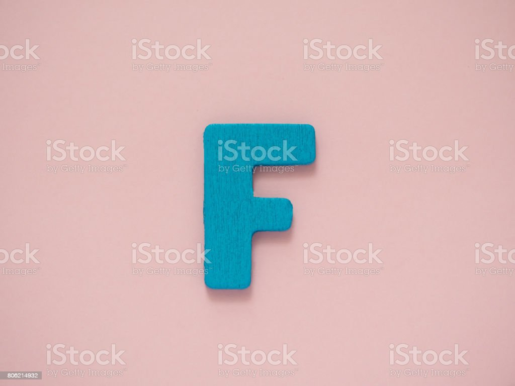 Capital letter F. Blue letter F from wood on pink background. stock photo