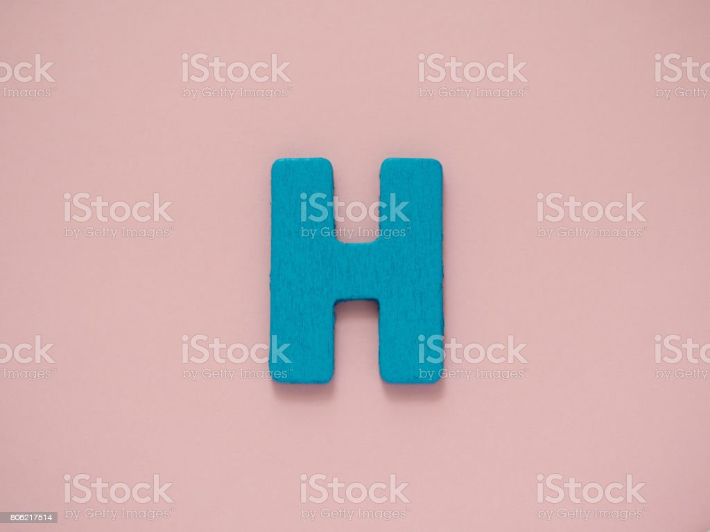 Capital letter H. Blue letter H from wood on pink background. stock photo
