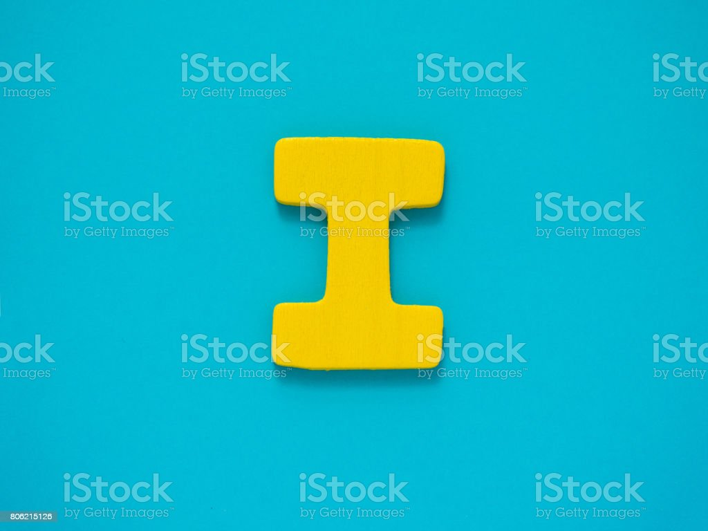 Capital letter I. Yellow letter I from wood on blue background. Alphabet vowel. stock photo