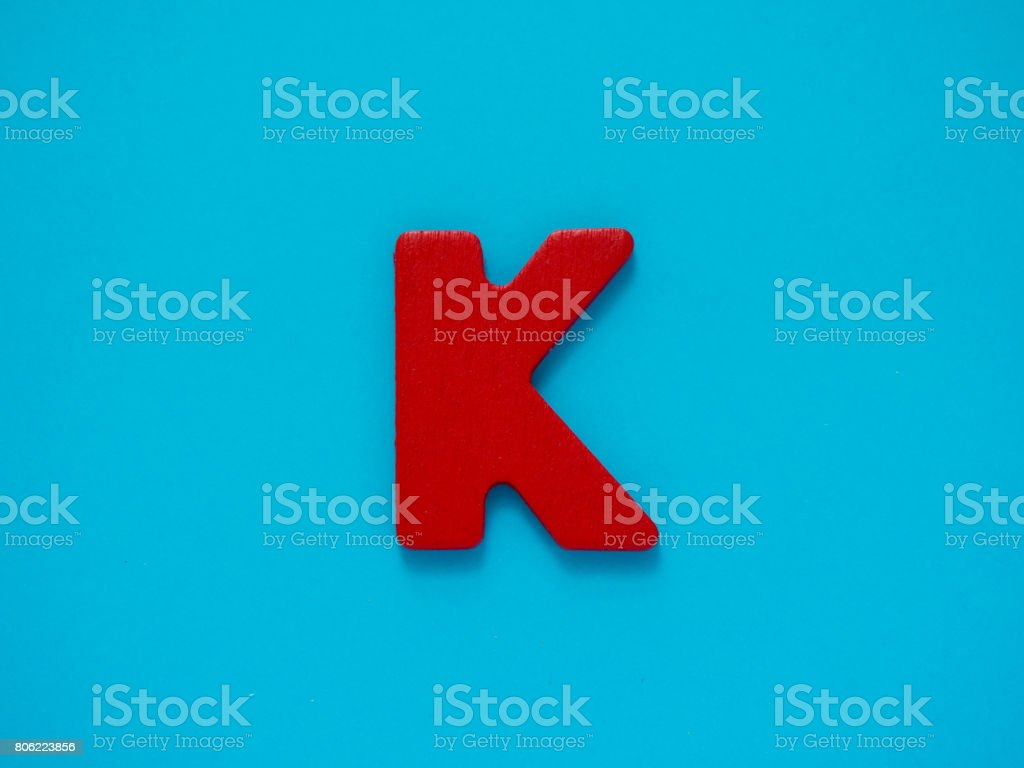 Capital letter K. Red letter K from wood on blue background. stock photo