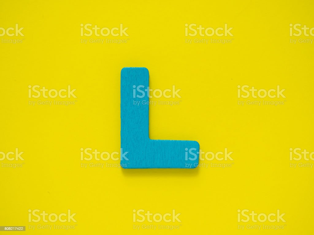 Capital letter L. Blue letter L from wood on Yellow background. stock photo